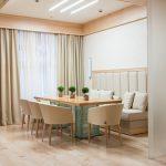 бежевая кухня, мягкие стулья за столом и диван